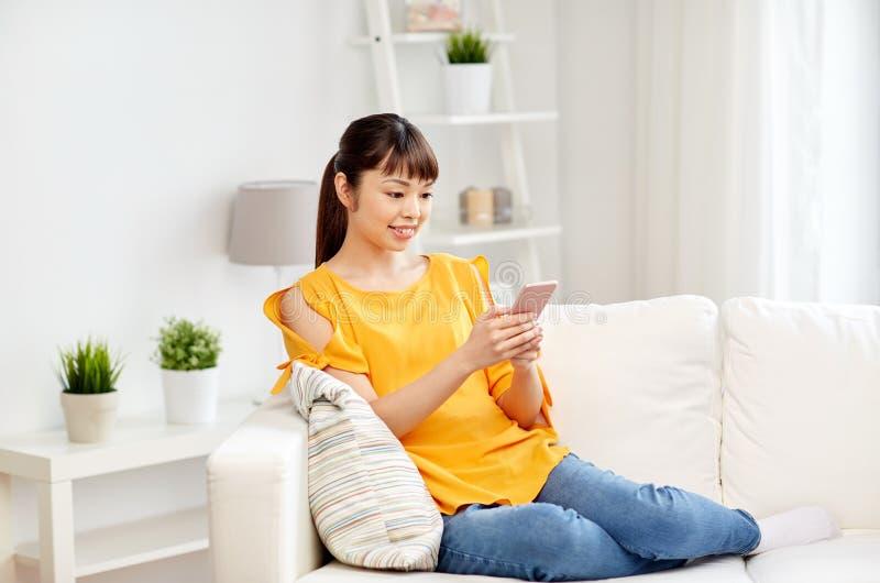 Mulher asiática feliz com smartphone em casa imagem de stock