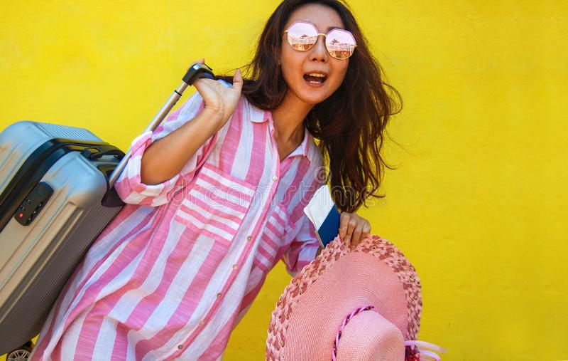 A mulher asiática feliz com uma mala de viagem e um bilhete está estando perto da parede amarela fotografia de stock
