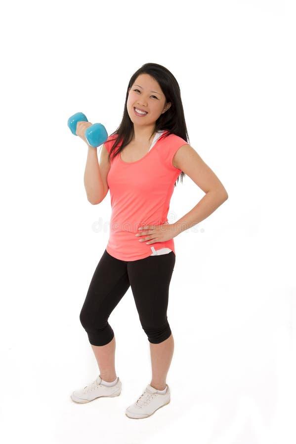 Mulher asiática feliz do esporte que guarda o peso de levantamento fotografia de stock