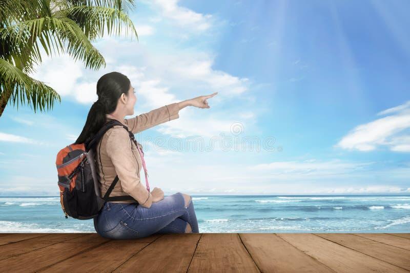 Mulher asiática feliz do turista que senta e que aprecia a vista para o mar fotografia de stock royalty free