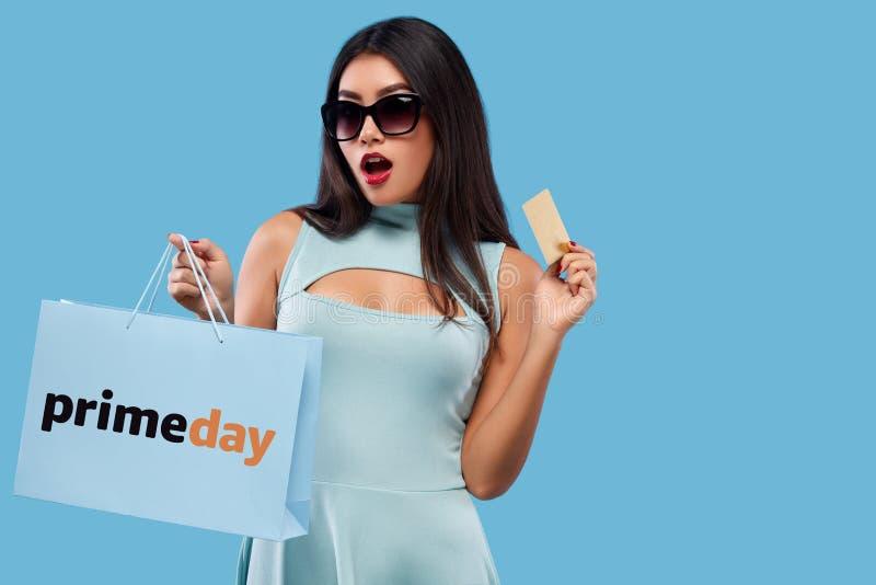 Mulher asiática feliz na compra que mantém o saco e o telefone isolados no fundo azul em sexta-feira preta e no feriado primeday imagem de stock royalty free