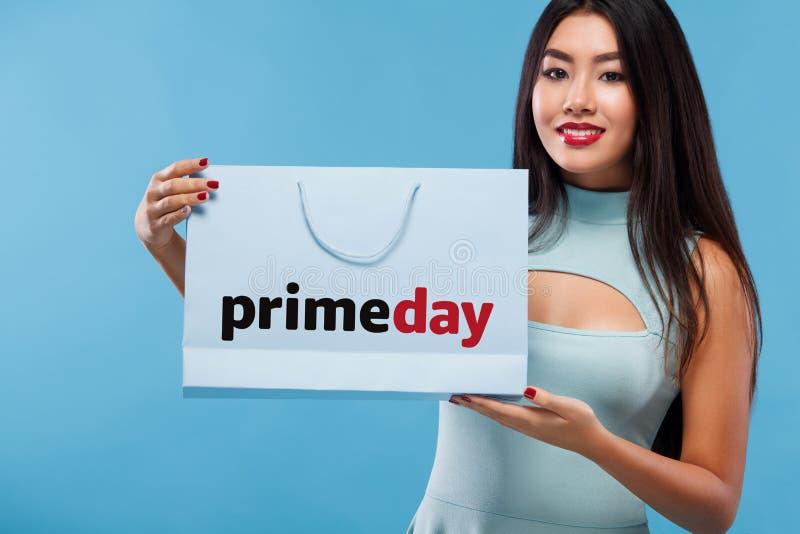 Mulher asiática feliz na compra que mantém o saco e o telefone isolados no fundo azul em sexta-feira preta e no feriado primeday imagens de stock