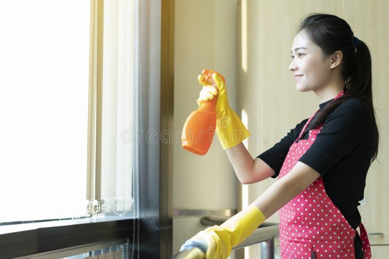 Mulher asiática feliz nas luvas que limpam com o limpador fotos de stock