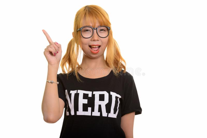 Mulher asiática feliz nova do lerdo que sorri e que aponta o dedo acima imagem de stock