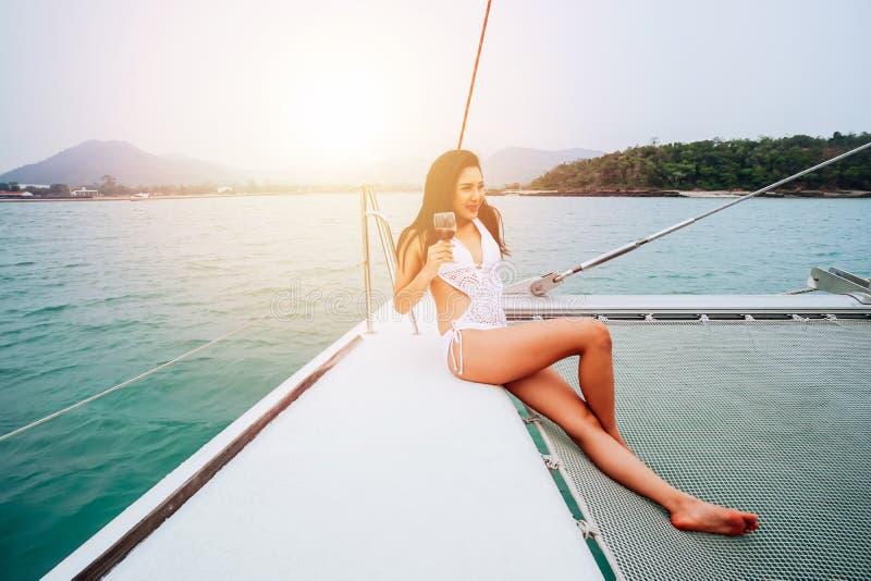 Mulher asi?tica feliz nova para apreciar e guardar um copo de vinho que senta-se na plataforma de navegar o barco do iate no biqu foto de stock