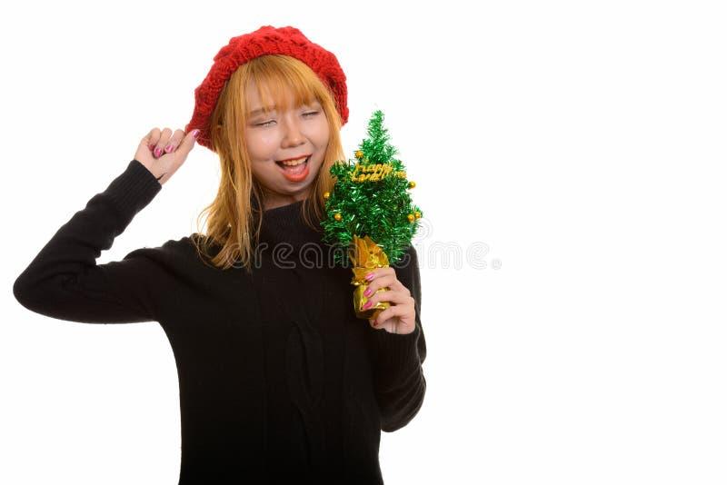 Mulher asiática feliz nova que sorri ao guardar o tre do ano novo feliz foto de stock royalty free