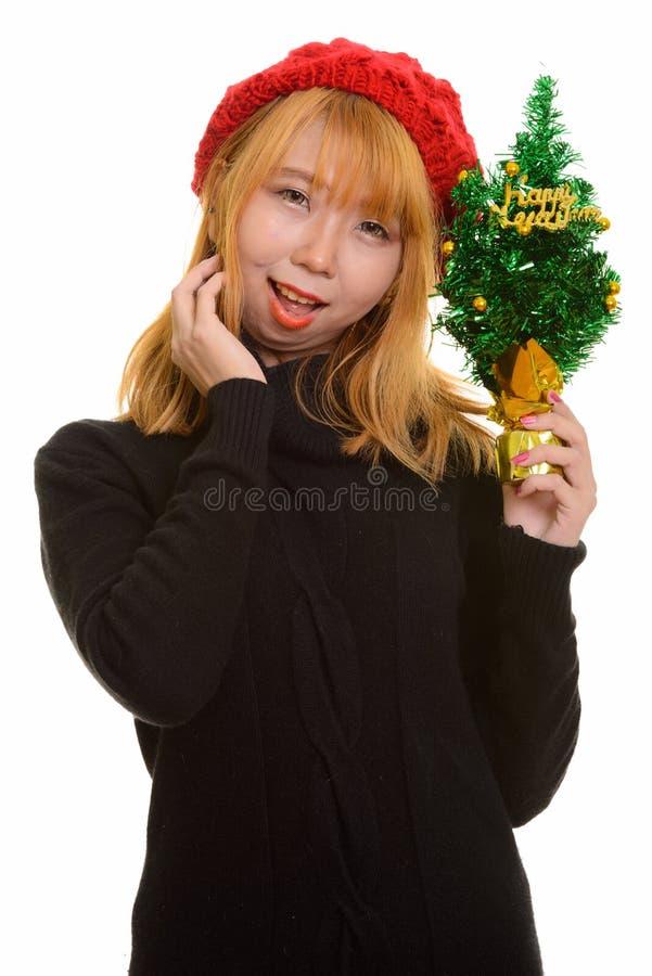 Mulher asiática feliz nova que sorri ao guardar o tre do ano novo feliz fotografia de stock royalty free