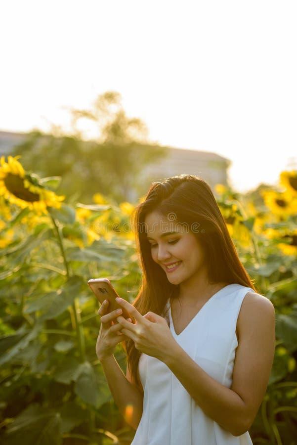 Mulher asiática feliz nova que sorri ao usar o telefone celular no imagens de stock