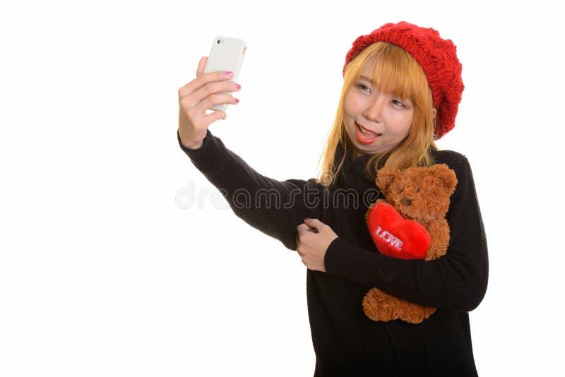 A mulher asiática feliz nova que sorri e que guarda o urso de peluche com ouve-se fotos de stock