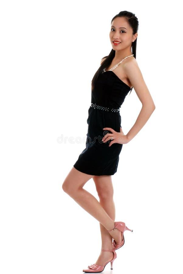 Mulher asiática feliz que desgasta um vestido preto isolado fotografia de stock