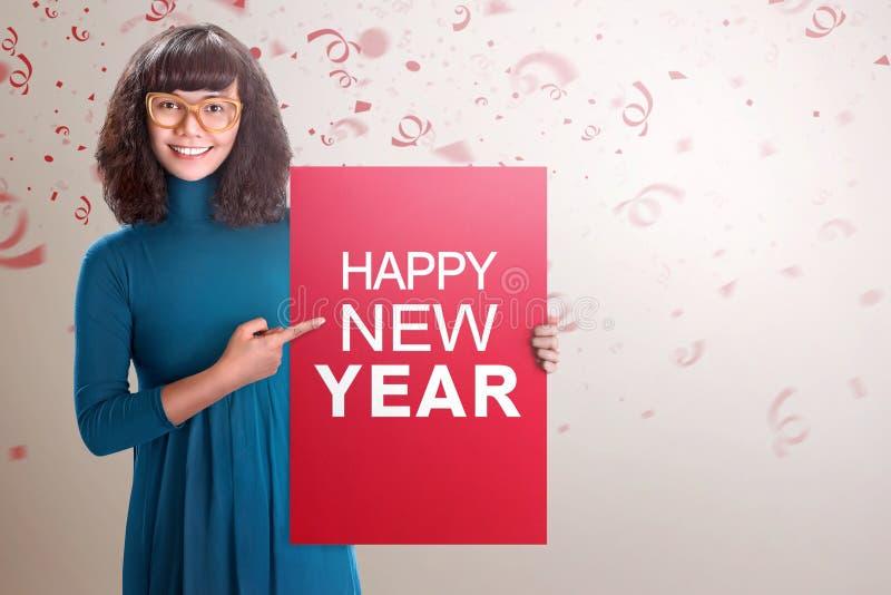 Mulher asiática feliz que mostra a placa vermelha com texto do ano novo feliz imagem de stock