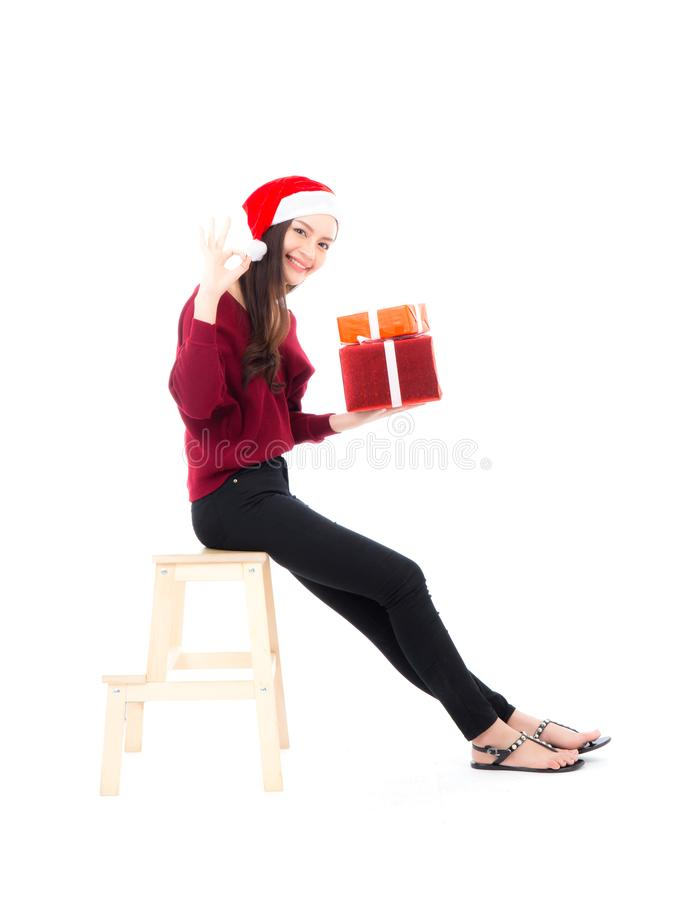 Mulher asiática feliz que senta com a caixa de presente da terra arrendada do sorriso muitos de xmas, menina atual com Natal da c imagem de stock