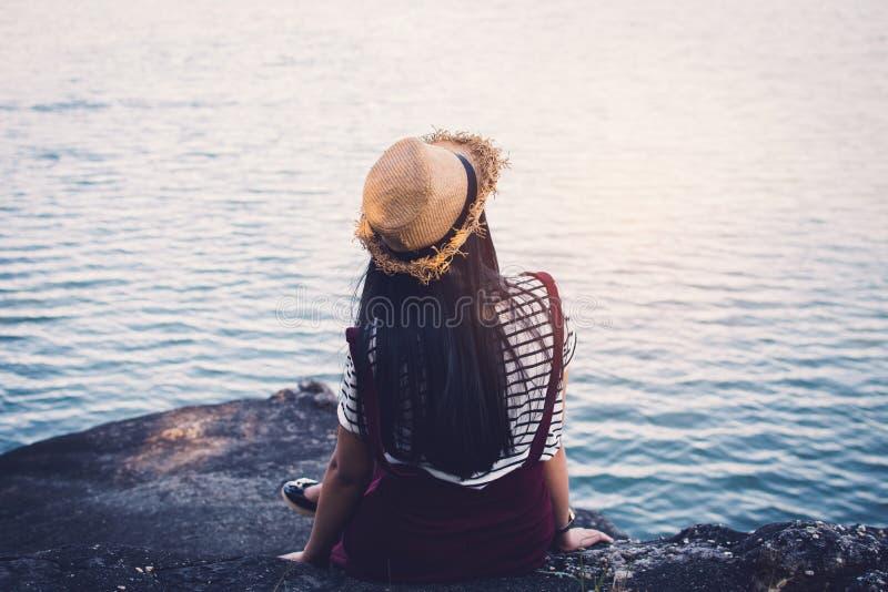 Mulher asiática feliz que senta-se na rocha na natureza foto de stock royalty free