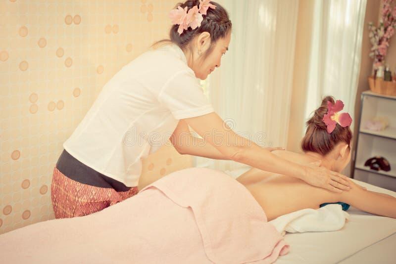 Mulher asiática feliz que tem a massagem traseira nos termas imagem de stock