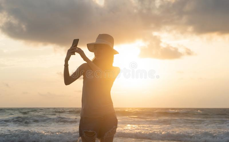 Mulher asiática feliz que toma um selfie para afixar fora em meios sociais na praia durante férias dos feriados do curso no ocean fotografia de stock