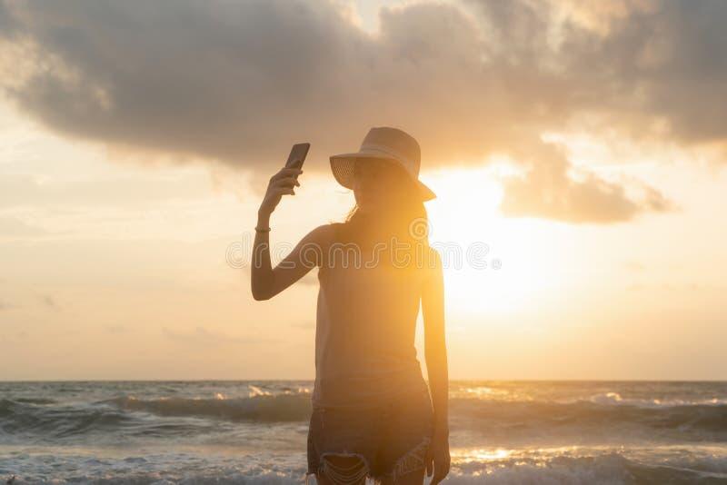 Mulher asiática feliz que toma um selfie para afixar fora em meios sociais na praia durante férias dos feriados do curso no ocean fotos de stock royalty free