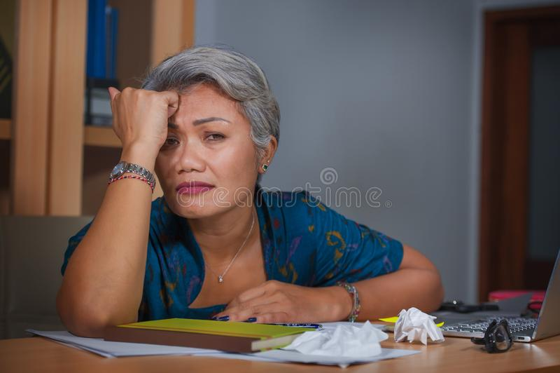 Mulher asiática forçada e sobrecarregado atrativa que trabalha na mesa do laptop do escritório no esforço que sente frustrado e v imagens de stock