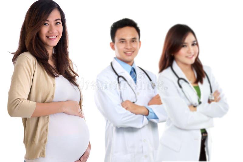 Mulher asiática grávida que está na frente de seu doutor foto de stock royalty free