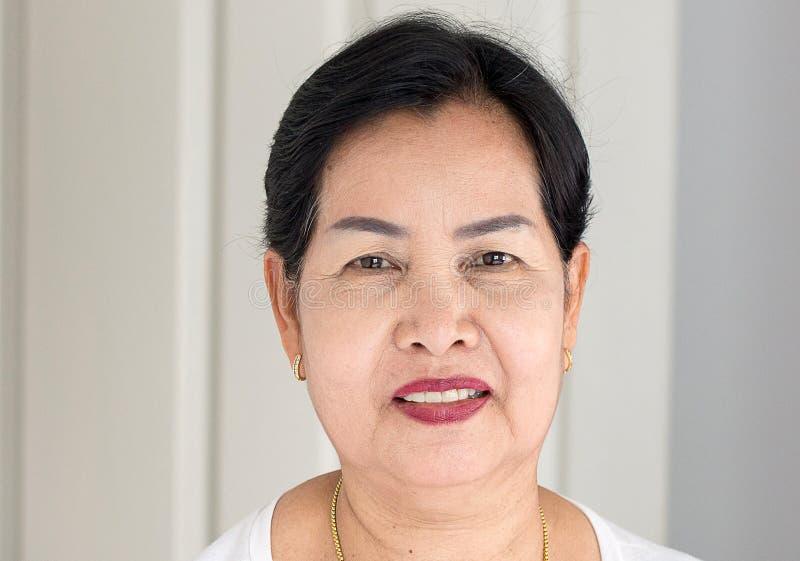 Mulher asiática idosa bonita na sala, em feliz fêmea superior e no sorriso, conceito do estilo de vida, positivo pensando, fim do imagens de stock