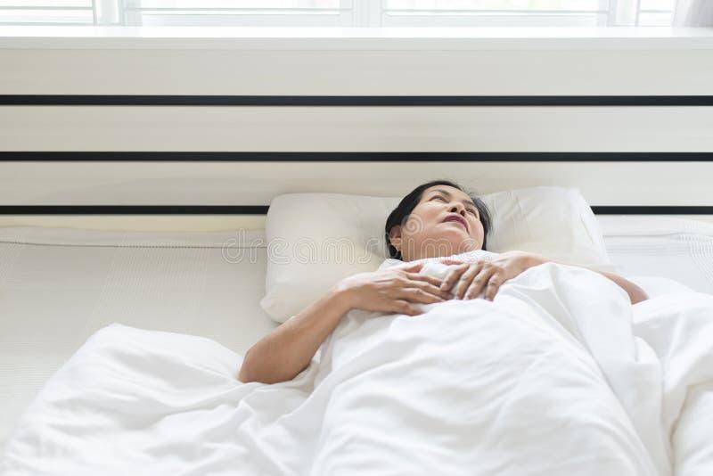 A mulher asiática idosa depressiva tem uma dor de cabeça e o sentimento considera seriamente no quarto fotografia de stock