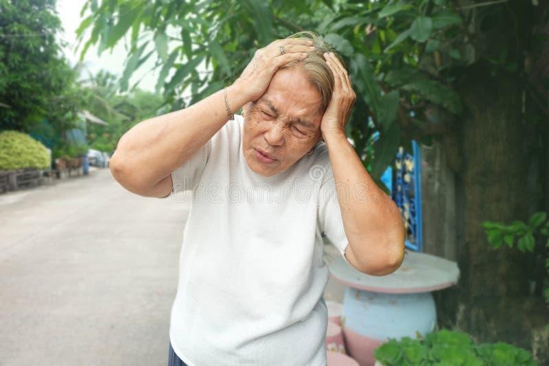 Mulher asiática idosa que guarda sua cabeça com dor de cabeça severa foto de stock royalty free