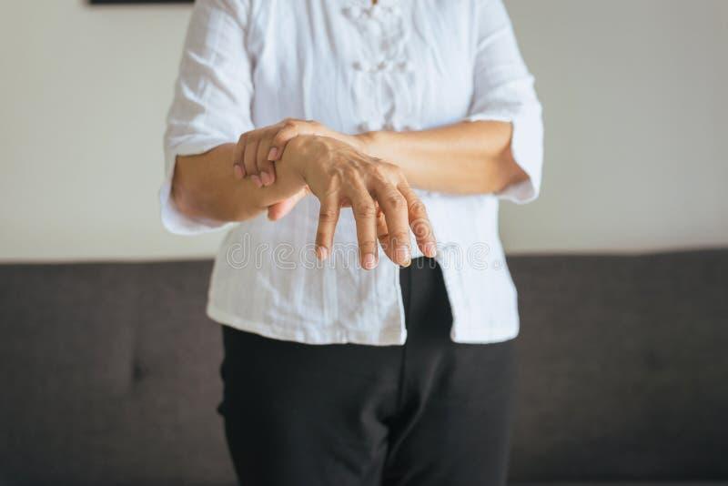 Mulher asiática idosa que sofre com sintomas da doença de Parkinson imagens de stock