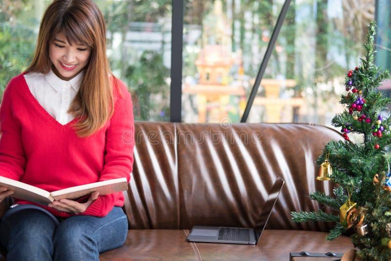 A mulher asiática leu o livro em casa a menina senta-se no sofá perto do Natal t fotos de stock royalty free