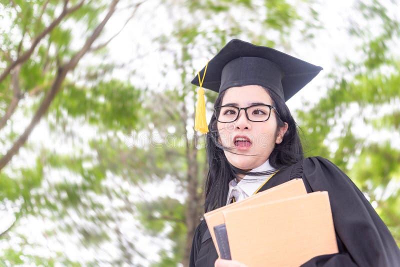 Mulher asiática louca nova que gradua-se guardando o diploma com orgulho e engraçada em um vestido acadêmico Fêmea da felicid foto de stock
