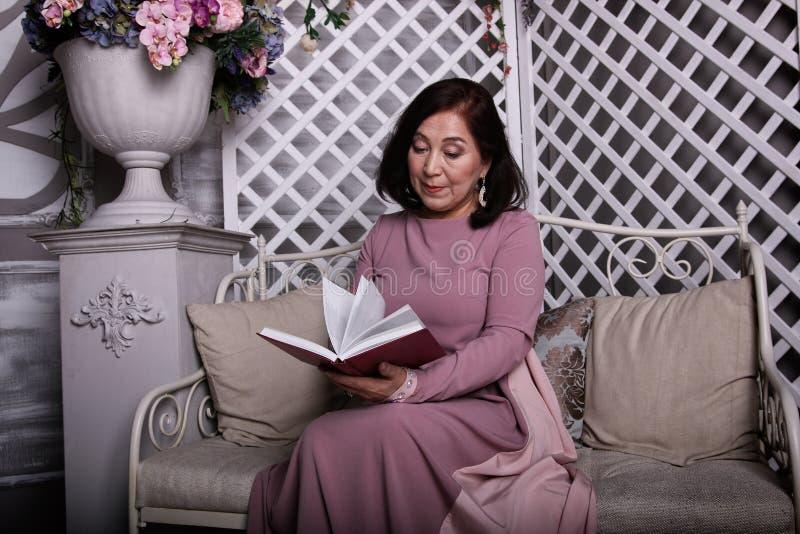 Mulher asiática madura que lê um livro em casa imagens de stock