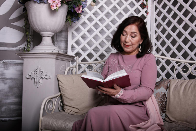 Mulher asiática madura que lê um livro em casa foto de stock royalty free