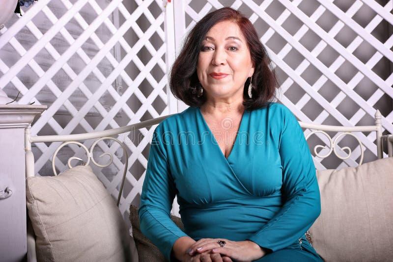 Mulher asiática madura que senta-se no sofá no vestido luxuoso imagens de stock