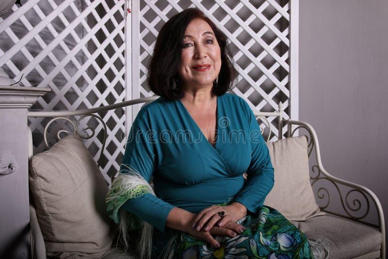 Mulher asiática madura que senta-se no sofá no vestido luxuoso foto de stock