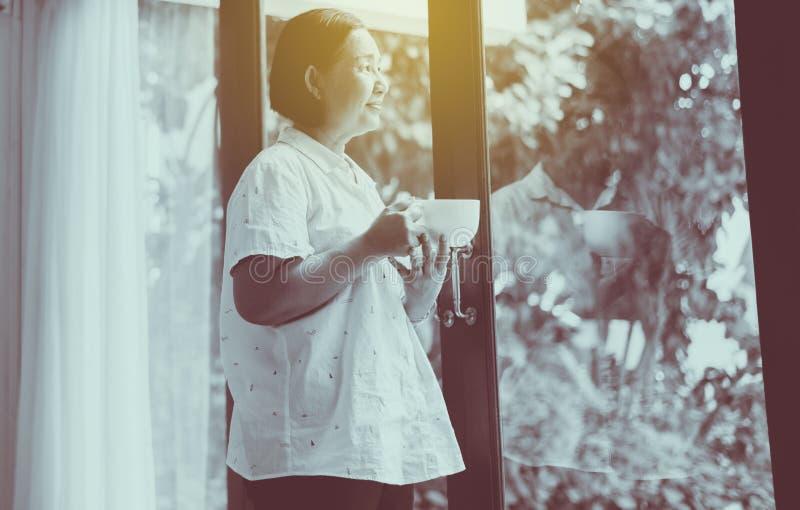 Mulher asiática madura segurando uma xícara de café quente perto da janela pela manhã,Feliz e sorridente,Pensamento positivo,Tons fotos de stock
