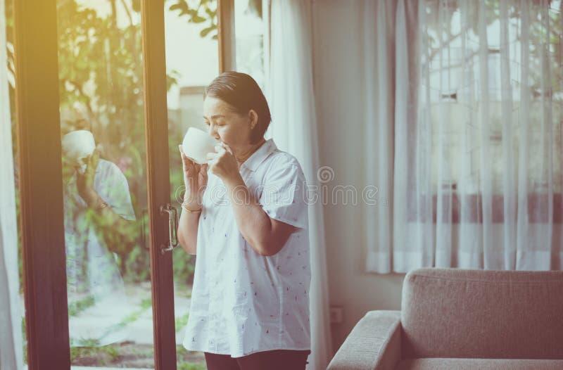 Mulher asiática madura tomando café quente perto da janela de manhã em casa, feliz e sorridente, pensamento positivo imagens de stock