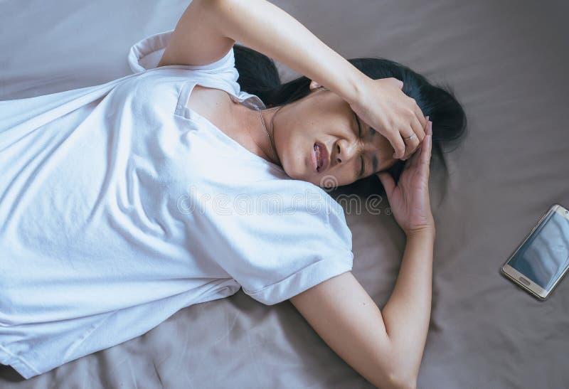 A mulher asiática manda uma dor de cabeça severa na cama após acordar foto de stock royalty free