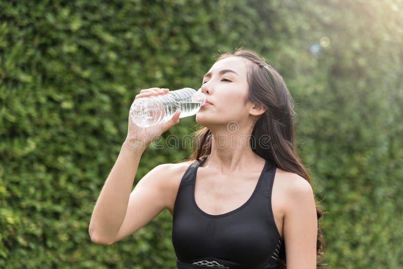 Mulher asiática na água potável do sportswear imagem de stock royalty free