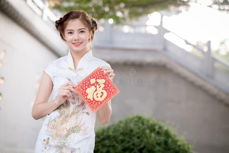 A mulher asiática no chinês veste manter o dístico 'feliz' (lombo imagem de stock royalty free