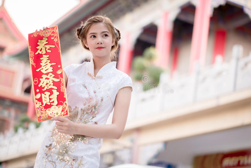 A mulher asiática no chinês veste manter o dístico 'lucrativo' (C fotos de stock royalty free