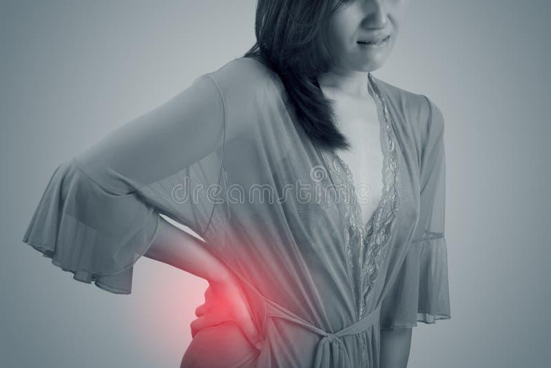 Mulher asiática no nightwear com dor na cintura e dor nas costas na noite imagens de stock royalty free
