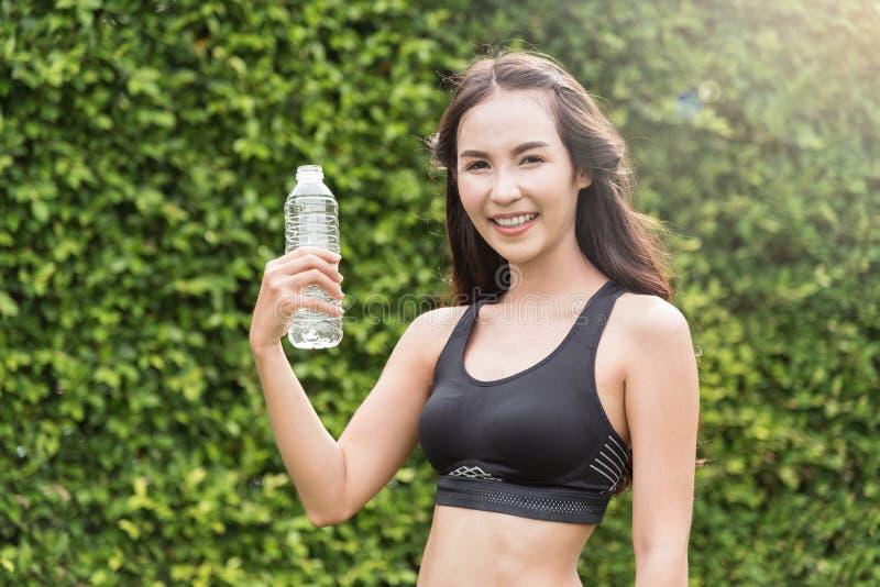 Mulher asiática no sportswear que guarda a garrafa da água imagens de stock