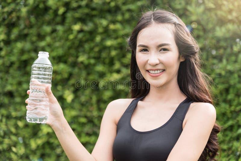 Mulher asiática no sportswear que guarda a garrafa da água no CCB natural imagens de stock royalty free