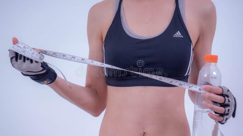 Mulher asiática no sutiã do esporte que mostra o corpo apto com fita métrica no fundo branco para a propaganda fotos de stock