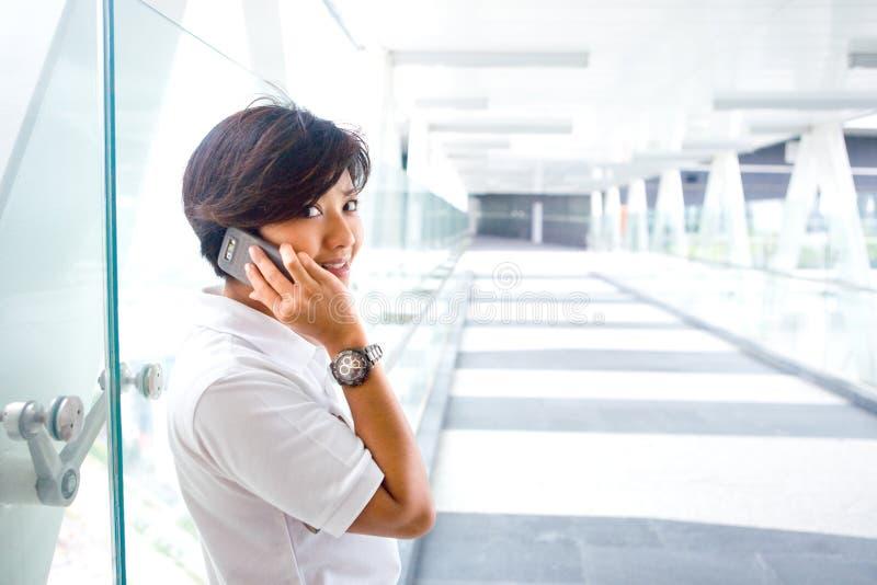 Mulher asiática no telemóvel no skybridge fotografia de stock