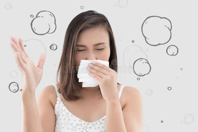A mulher asiática no vestido branco trava seu nariz devido a um cheiro mau fotos de stock royalty free