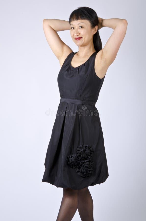 Mulher asiática no vestido de partido preto foto de stock
