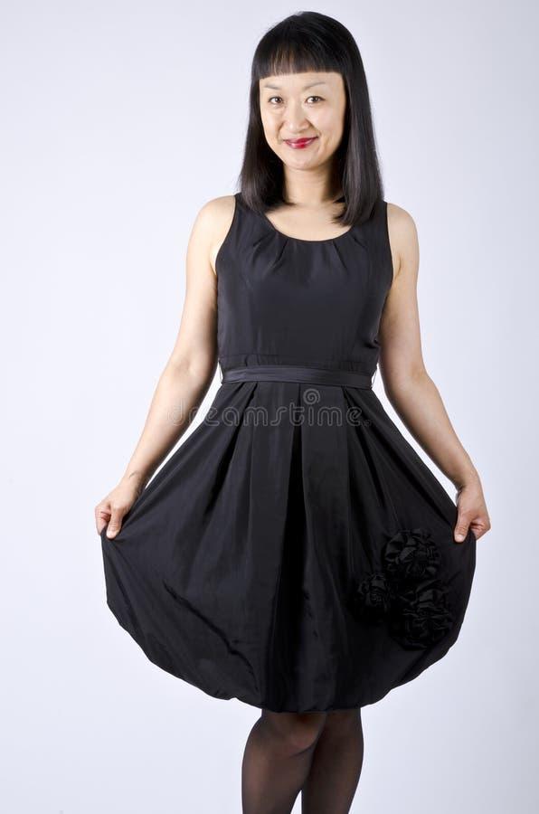 Mulher asiática no vestido de partido preto imagens de stock royalty free