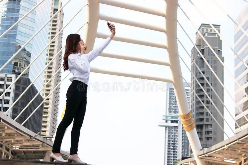 Mulher asiática nova alegre que toma uma foto do selfie na construção urbana com fundo do espaço da cópia imagem de stock royalty free