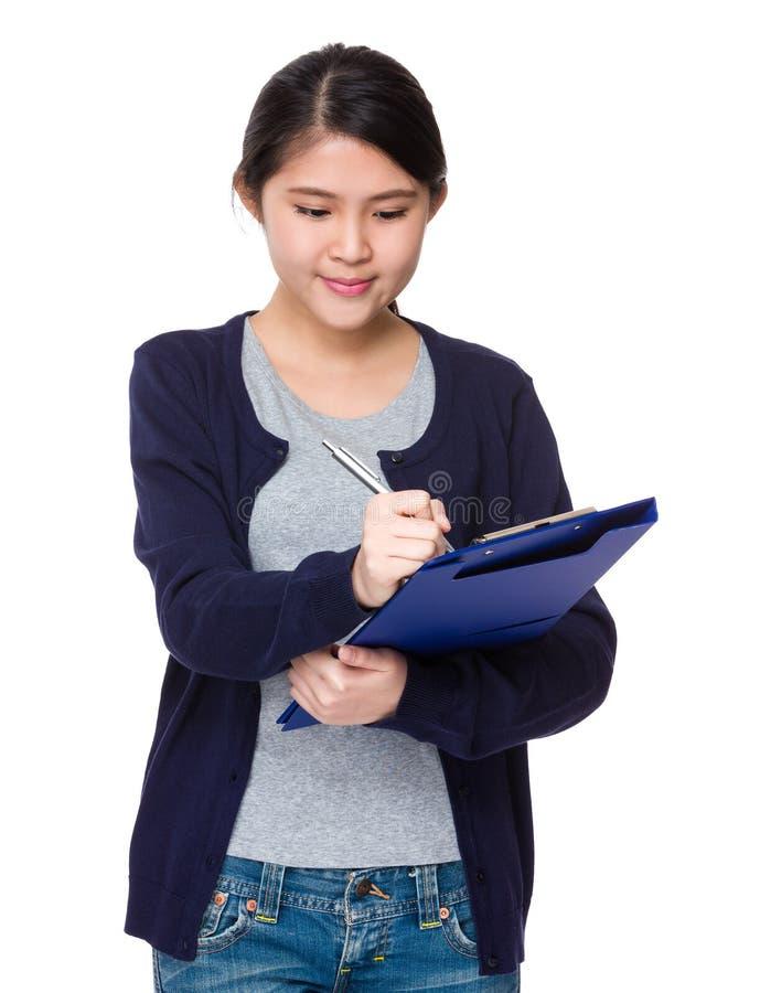 A mulher asiática nova anota o memorando na placa do arquivo foto de stock