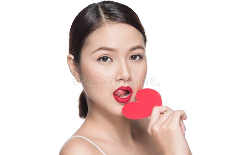 Mulher asiática nova atrativa que guarda o coração vermelho Dia do `s do Valentim imagem de stock royalty free
