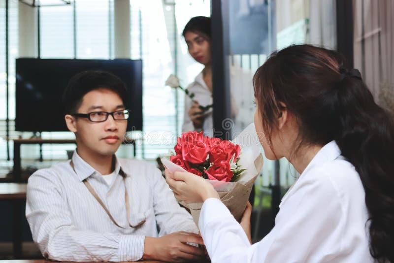 Mulher asiática nova atrativa surpreendida que aceita um ramalhete de rosas vermelhas do noivo com fundo irritado invejoso da mul fotografia de stock